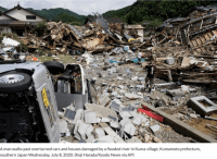 A man walks past overturned cars and houses damaged by a flooded river in Kuma village, Kumamoto prefecture, southern Japan.