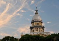 The dome of the Illinois State Capitol over a cluster of trees.