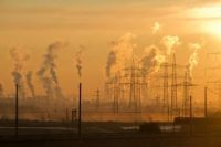 Smokestacks and electrical towers silhouetted by a golden orange sky.