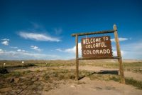 """A wooden sign reads """"welcome to colorful Colorado."""""""