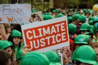 """A person holds a red sign reading """"climate justice"""""""