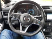 The steering wheel of a Nissan Leaf from the angle of a person sitting in the driver's seat.
