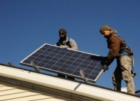 A pair of solar installers line up a panel atop a home.