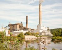 Merrimack Station coal-fired power plant, which sits on the shore of the Merrimack River, whose waters can be seen in the foreground.