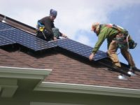 Workers install solar panels on a roof.