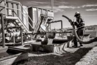 An oil worker carries a pipe.
