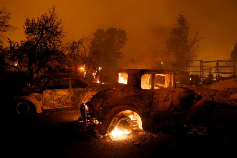 Classic cars burn at a home at Neal Road as wildfires swept in