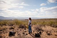 A man in a white T-shirt and jeans stands in a desert surrounded by rocks, pointing toward mountains in the distance.