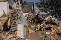 People rest after working to clear out a street in Altenahr , Germany, following davastating floods.