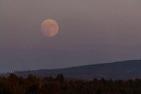 The full moon rises over the hills shrouded in smoke from wildfires
