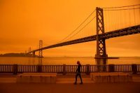 A woman walks along the Embarcadero under an orange smoke-filled sky in San Francisco during the 2020 wildfire season