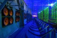 Industrial cooling fans operate to thermally regulate illuminated mining rigs at the CryptoUniverse cryptocurrency mining farm in Nadvoitsy, Russia, on Thursday, March 18, 2021.