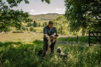 James Rebanks walks with his border collies in June on his farm in Matterdale, England