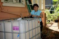 Joan Voight in her side yard with her 275-gallon recycled water tank.