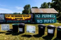 Pipeline protest signs form a backdrop to waste segregation bins at a campsite on the White Earth Nation Reservation near Waubun