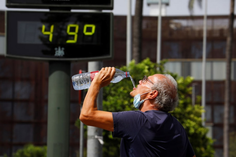 Guy drinking water hot day