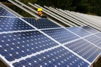 A person in a hard hat assembles solar panels.