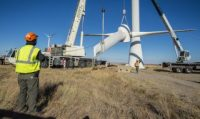 Engineers and technicians lower the rotor and blades off of a wind turbine.