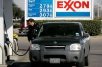 A customer pumps fuel into his vehicle at an Exxon gas station.