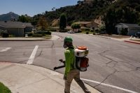 A representative of the company Mosquito Squad performs a house call in the Glendale, Calif., area on Sept. 13.