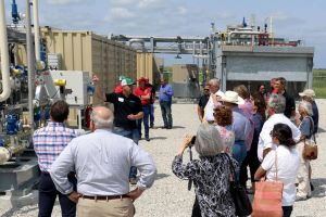 James Thomas, center in black, a regional operations manager with Roeslein Alternative Energy, educates state politicians about the company's methane gas project at a farm in Somerset, Missouri