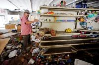 John Curtis, a co-owner of Waverly Cash Saver grocery store, walking through his damaged store on Sunday in Waverly, Tenn.