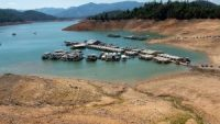 Low water levels expose the bottom of Lake Shasta as boats and docks float in the water near the Bridge Bay