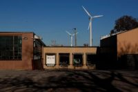 Wind turbines are seen behind a factory in Cleveland in this photo dated Nov. 9, 2020