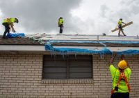 Workers installed a temporary roof on a home in New Orleans last week that was damaged by Hurricane Ida