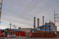 A power plant with three smokestacks and power lines running to it.
