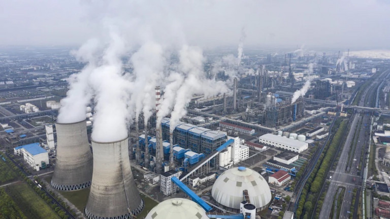 Exhaust rises from smokestacks and cooling towers at the Sinopec Zhenhai Refining & Chemical Co. processing facility on the outskirts of Ningbo, China