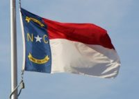 The flag of North Carolina billows from a flagpole.